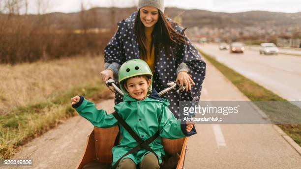 cargo bike ride on the rain - mother son shower stock photos and pictures