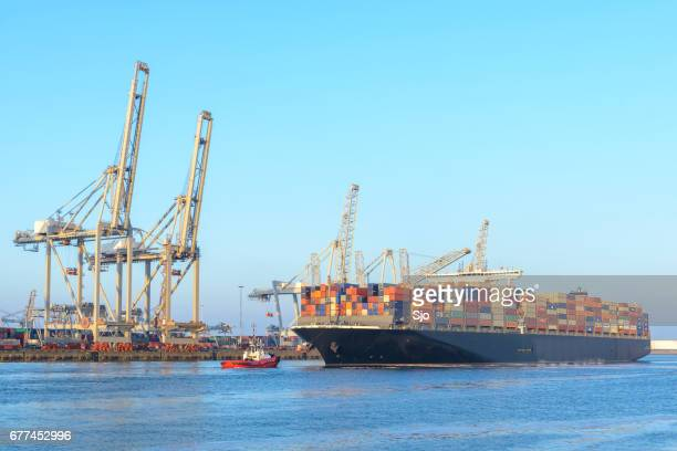 cargo container ship at a container terminal in rotterdam port - rotterdam stock pictures, royalty-free photos & images