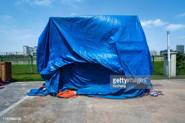cargo covered with tarpaulin - tarpaulin stock pictures, royalty-free photos & images
