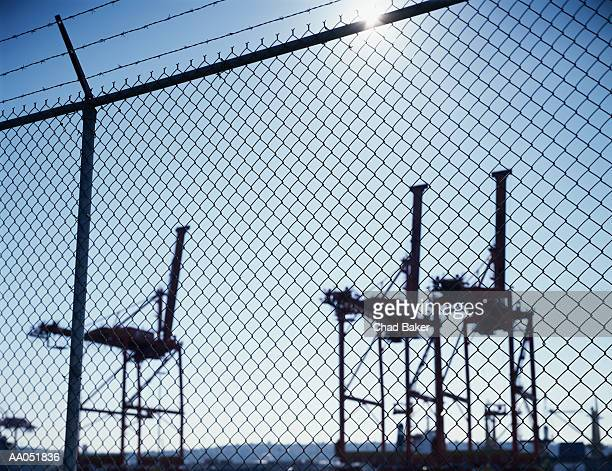Cargo cranes in harbor, view through chain link fence, dusk