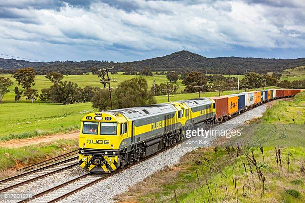 qube cargo freight train passing through rural countryside - rail freight stock pictures, royalty-free photos & images