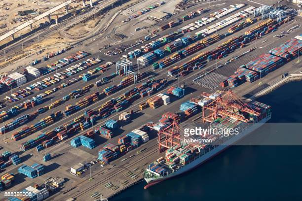 cargo ship being loaded at the port of long beach - long beach california stock photos and pictures