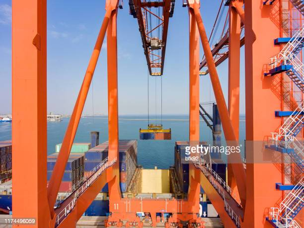 cargo ship being loaded with containers at port. - shipyard stock pictures, royalty-free photos & images