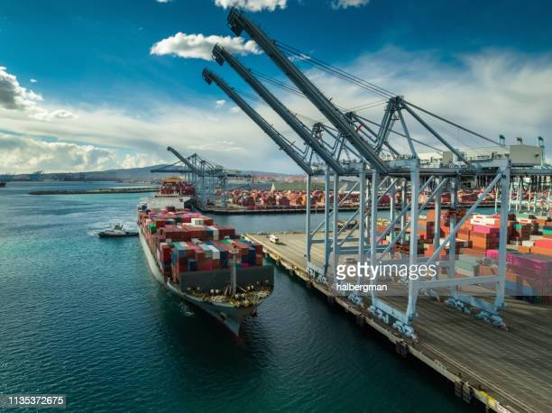 cargo ship being pushed beneath container cranes in port - aerial - long beach california stock pictures, royalty-free photos & images