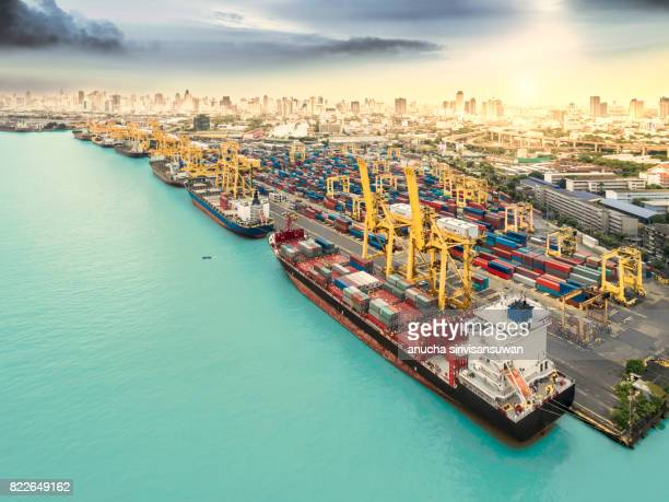 cargo ship container park at the pier near city at sunset . - international match stock pictures, royalty-free photos & images