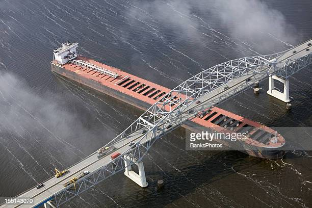 Cargo Ship Enters Port under Bridge Aerial