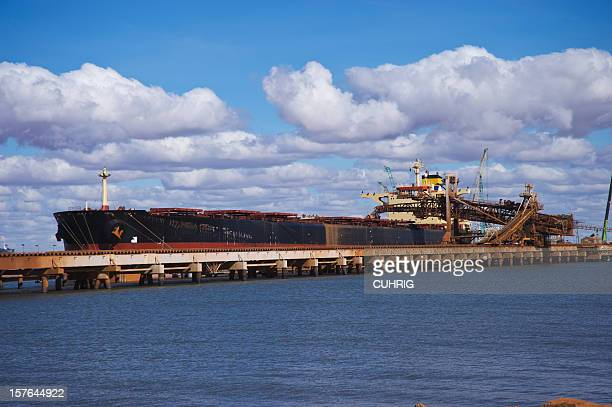 cargo ship in port loading iron ore - iron ore stock photos and pictures