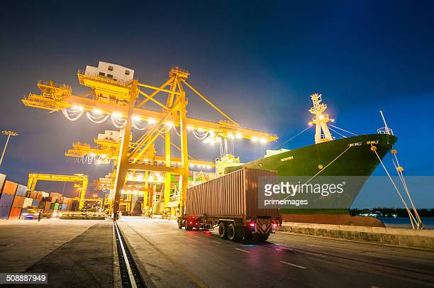 cargo ship in the harbor at sunset . - commercial dock stock pictures, royalty-free photos & images