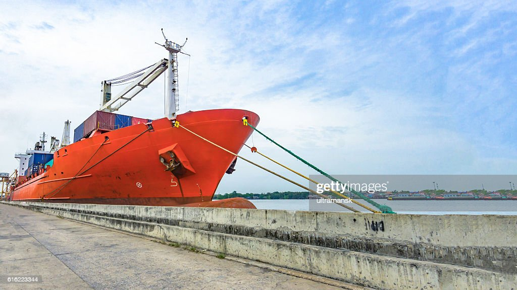 Cargo ship in the harbor with the river and sea : Stockfoto