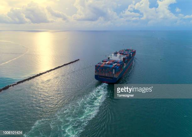 cargo ship leaving port - cargo ship stock pictures, royalty-free photos & images