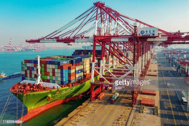 Cargo ship loaded with containers berths at a port in Qingdao in China's eastern Shandong province on January 14, 2020. - China's trade surplus with...