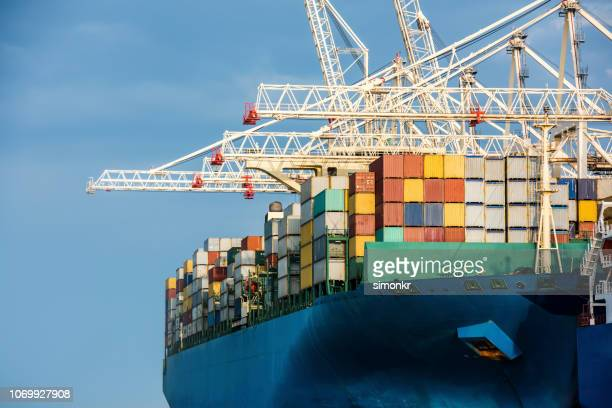 cargo ship moored while being loaded with containers - container ship stock pictures, royalty-free photos & images