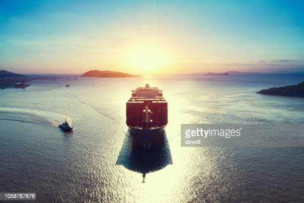 cargo ship over sea with sunrsie - cargo ship stock pictures, royalty-free photos & images