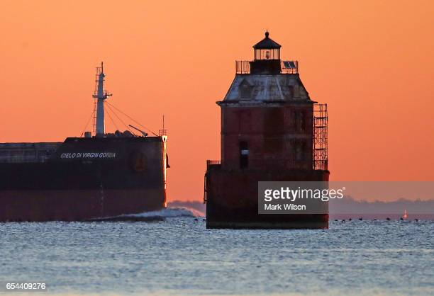 A cargo ship passes the Sandy Point Shoal Lighthouse on the Chesapeake Bay on March 17 2017 in Skidmore Maryland Under US President Donald Trump's...