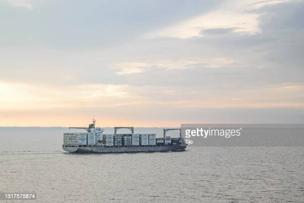 """cargo ship passing on the great belt strait in denmark during sunset - """"sjoerd van der wal"""" or """"sjo"""" stock pictures, royalty-free photos & images"""