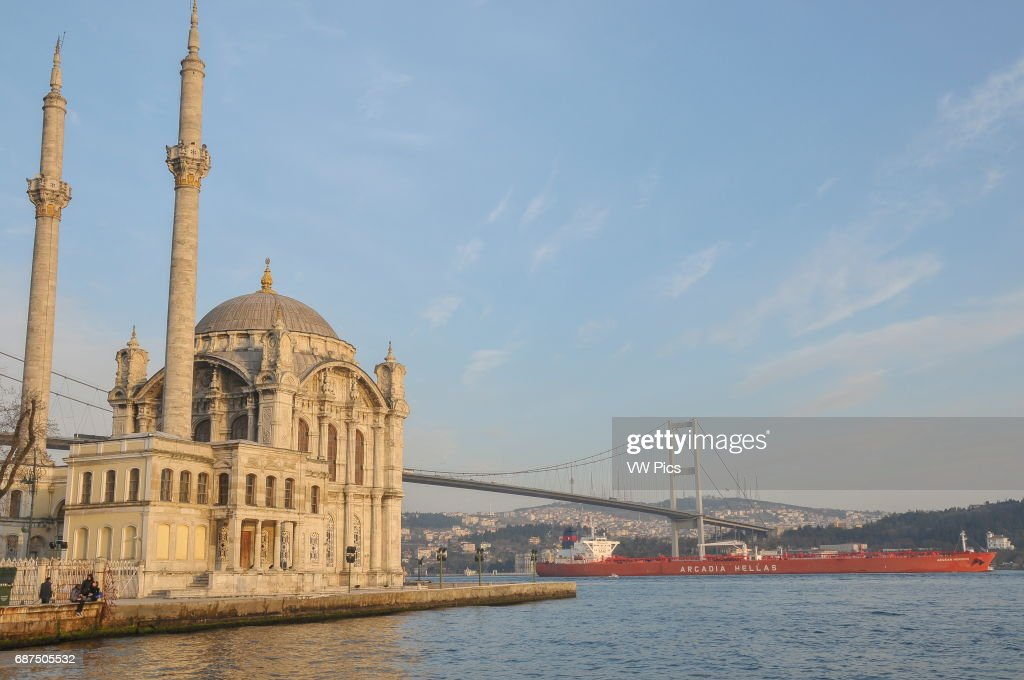 A cargo ship sails down the Bosphorus from the Black Sea towards the Sea of Marmara, past Ortak_y mosque and the first Bosphorus bridge.