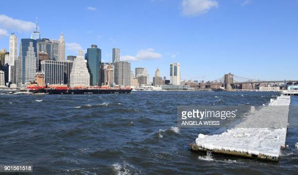 A cargo ship sails past a pier covered in snow and ice floating in the East River in Brooklyn New York on January 5 2018 The National Weather Service...