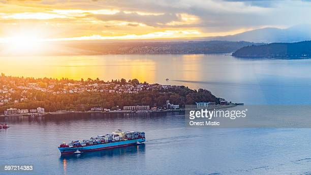 cargo ship through puget sound in sunset - puget sound stock pictures, royalty-free photos & images