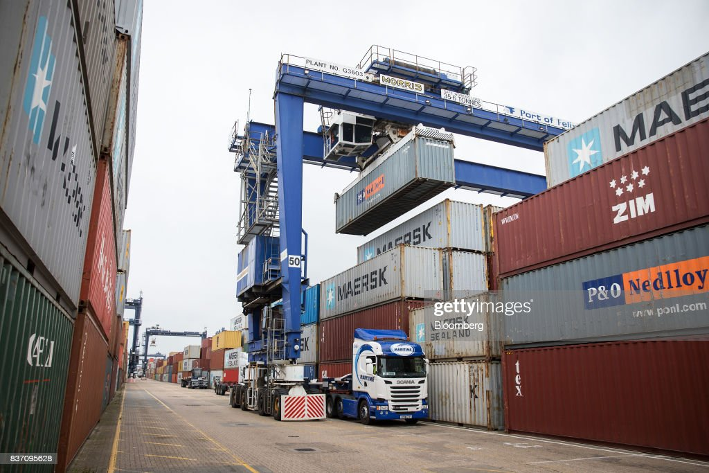 A cargo shipping container is loaded onto a freight truck at the Port of Felixstowe Ltd., a subsidiary of CK Hutchison Holdings Ltd. in Felixstowe, U.K., on Tuesday, Aug. 22, 2017. U.K. exporters are still reaping the benefits of a weaker pound, but they're not sure how long the boost will continue as the country gets closer to withdrawing from the European Union. Photographer: Simon Dawson/Bloomberg via Getty Images