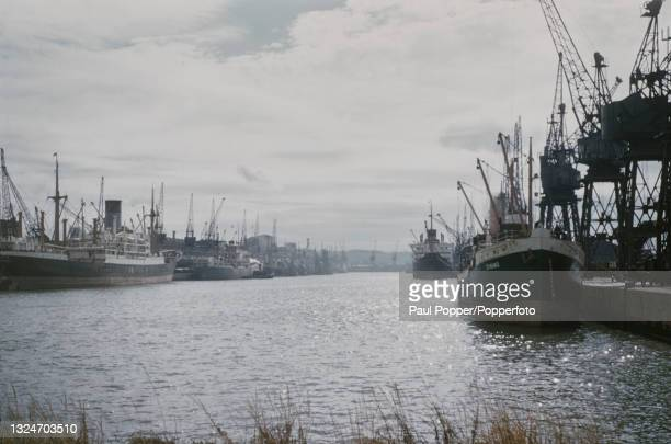 Cargo ships and freighters moored next to dockside cranes at Avonmouth Docks, part of the Port of Bristol, near Bristol in England circa 1960.