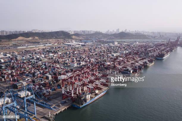 Cargo ships are moored under cranes as shipping containers stand at the Qingdao Qianwan Container Terminal in this aerial photograph taken in Qingdao...