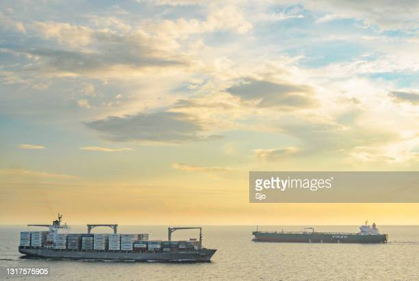 """cargo ships passing on the great belt strait in denmark during sunset - """"sjoerd van der wal"""" or """"sjo"""" stock pictures, royalty-free photos & images"""