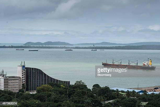 Cargo ships sit in the waterway beyond buildings on the waterfront in Conakry Guinea on Saturday Sept 5 2015 While Guinea produces bauxite which is...