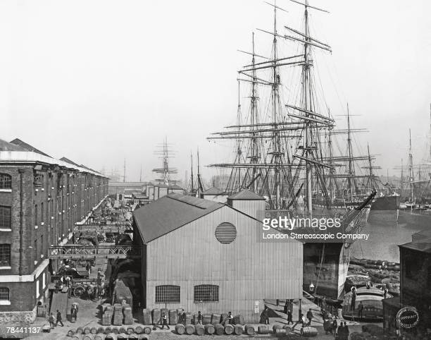 Cargo stacked by warehouses on the waterfront at a busy London dock where a large sailing ship is moored circa 1893