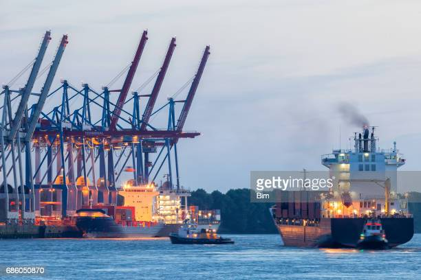 Cargo Terminal, Large Container Ship Assisted By Tugboats in Hamburg Harbor, Germany
