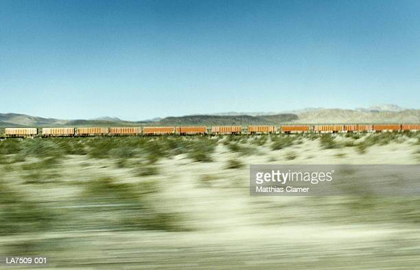 cargo train crossing desert, california, usa (blurred motion) - rail freight stock pictures, royalty-free photos & images