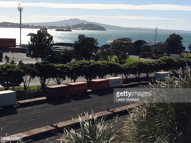 cargo train leaving Auckland docks with Rangitoto volcanic island in the distance New Zealand