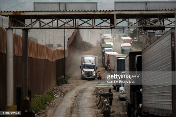 TOPSHOT Cargo trucks line up next to the border fence to cross to the United States near the USMexico border at Otay Mesa crossing port in Tijuana...