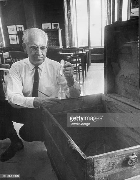 AUG 22 1965 Carhart Checks Conservation Mementoes Kneeling beside one of three trunks which contained records of the US Bison Society Carhart holds...
