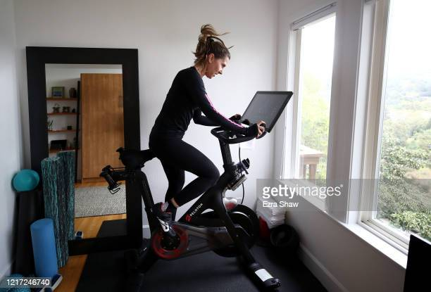 Cari Gundee rides her Peloton exercise bike at her home on April 06, 2020 in San Anselmo, California. More people are turning to Peloton due to...