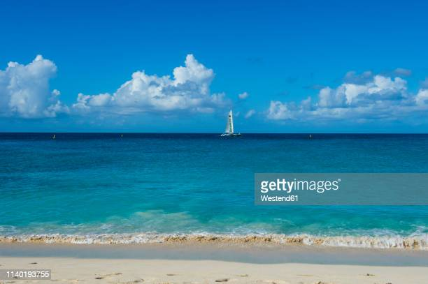 caribbean, antilles, sint maarten, beach at maho bay, sailing boat - sint maarten caraïbisch eiland stockfoto's en -beelden