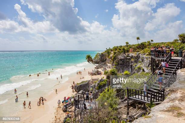 caribbean beach life on cliffs on maya ruins of tulum - mexico - tulum mexico stock photos and pictures