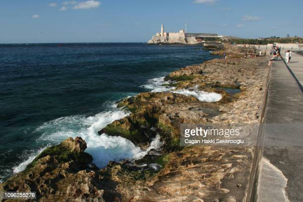 caribbean ocean seen from the famous malecon or avenida de maceo, with the morro castle or castillo de los tres reyes del morro, in the background - três pessoas stock pictures, royalty-free photos & images