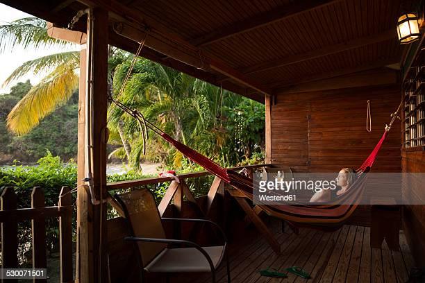 Caribbean, Trinidad and Tobago, Tobago, Castara, woman in hamock on porch