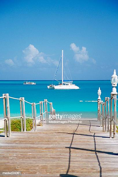 caribbean, turks and caicos islands, providenciales, grace bay beach, boardwalk over a sea - grand bahama stock photos and pictures