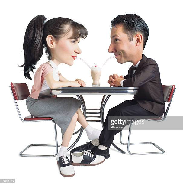 caricature of caucasian 50s era young couple as they share a soda and play footsies at a malt shop