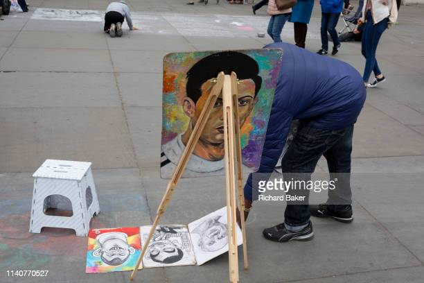 A caricature street artist lays out his portrait examples on the pavement in Trafalgar Square on 2nd May 2019 in London England