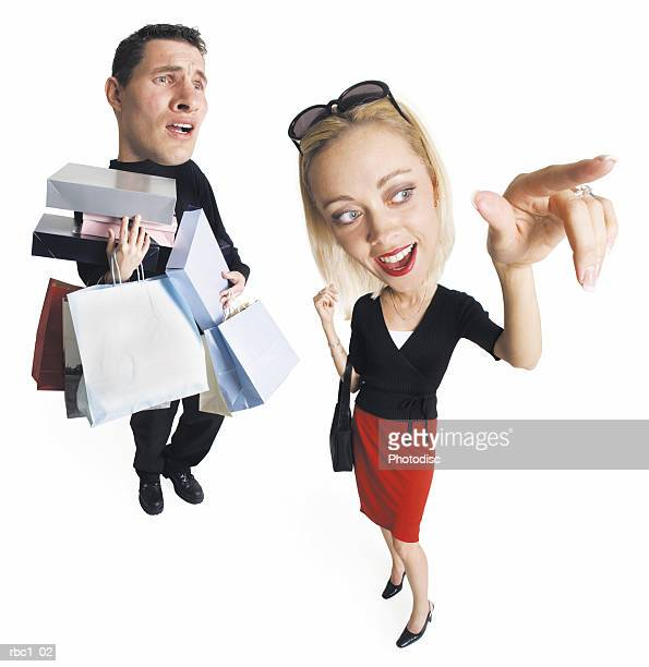 caricature young caucasian couple shopping the man carries many bags packages as blonde woman points - karikatuur stockfoto's en -beelden