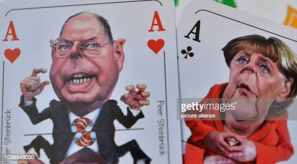 Caricatures of Federal Chancellor Angela Merkel and her challenger Peer Steinbrueck can be seen on a new skat game of the card factory in Altenburg...