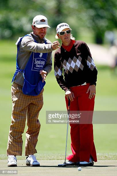 Carin Koch of Sweden talks with her caddie prior to a putt on the 9th hole during the second round of the SemGroup Championship presented by John Q...