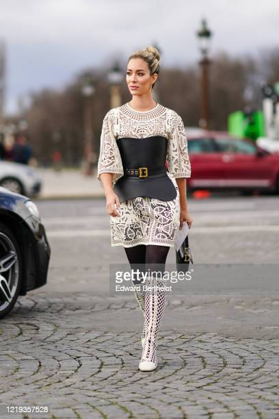 Carin Olsson wears a white mesh dress with embroidery a black leather Dior belt a bustier a Dior Saddle bag tights white mesh lace up boots outside...