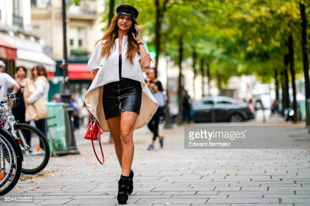 Carina Zavline wears a black hat a white shirt a black skirt a red bag outside Koche during Paris Fashion Week Womenswear Spring/Summer 2018 on...