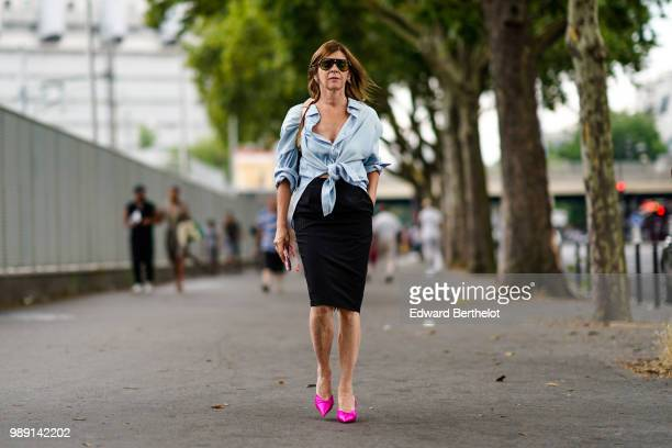 Carine Roitfeld wears a blue shirt a black skirt pink shoes outside Vetements during Paris Fashion Week Haute Couture Fall Winter 2018/2019 on July 1...