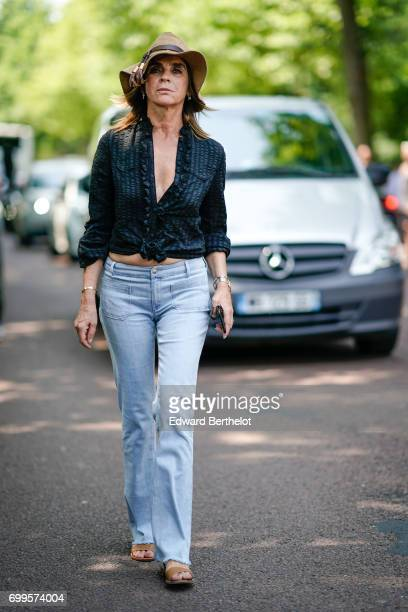 Carine Roitfeld wears a camel hat a black low neck shirt blue denim jeans pants outside the Balenciaga show during Paris Fashion Week Menswear...