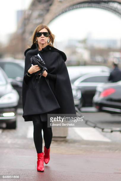 Carine Roitfeld wears sunglasses a black cape black leggings and red leather boots outside the Hermes show during Paris Fashion Week Womenswear...