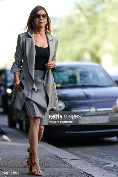 Carine Roitfeld wears sunglasses a gray blazer jacket a gray skirt a black top and heels after the CDG Comme des Garcons show during Paris Fashion...